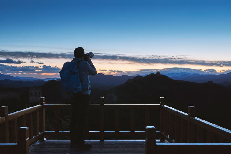 Rear view of mature man photographing with camera while standing on observation point against blue sky during sunset