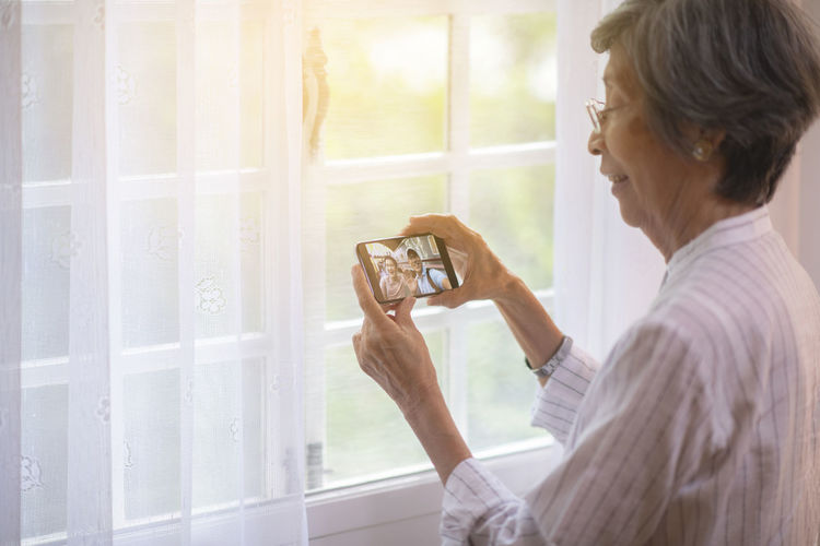 Midsection of woman photographing through smart phone at window