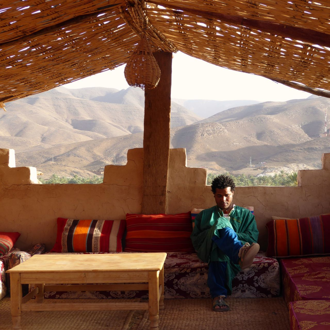 Man Relaxing On Sofa At Hotel Roof Terrace With Mountains In Background