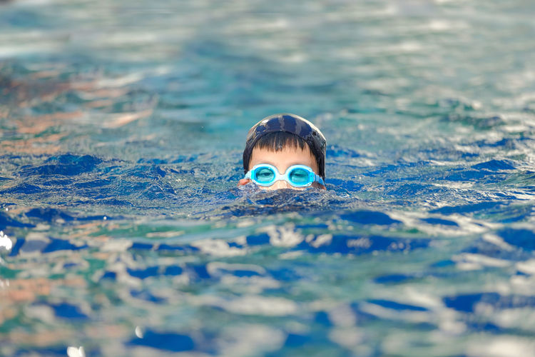 Portrait of boy wearing goggles swimming in pool