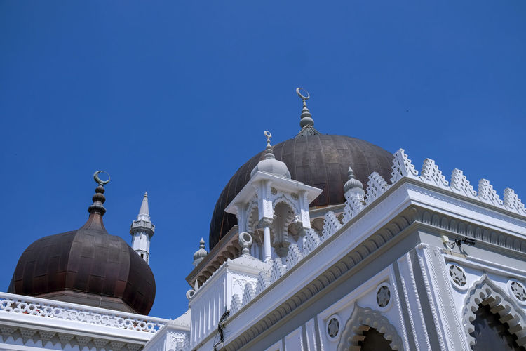 Low angle view of mosque against clear blue sky
