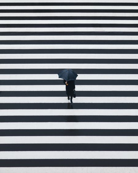 High angle view of person holding umbrella while walking on crosswalk