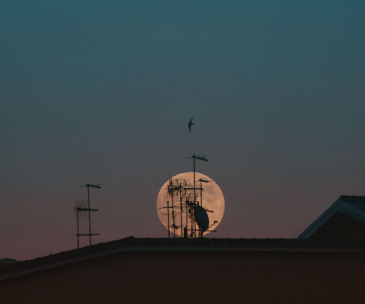Sky Architecture Built Structure Antenna - Aerial Communication Satellite Technology Telecommunications Equipment Nature Satellite Dish Outdoors Roof Moon Nature Full Moon Contrast Moon Rising City Building Sunset No People Wireless Technology Global Communications Connection Building Exterior