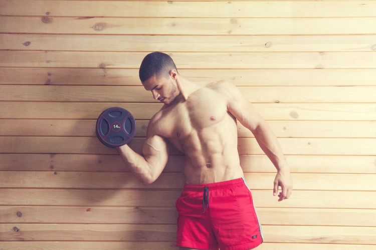 Shirtless Man Exercising Against Wooden Wall