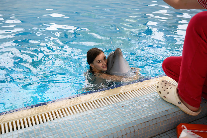 Man crouching by woman with dolphin in swimming pool