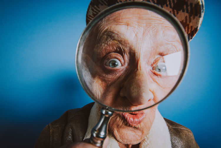 Close-up portrait of senior man looking through magnifying glass against blue background