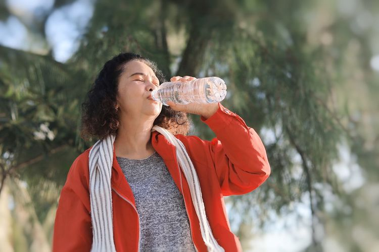 Midsection of woman holding drink against trees