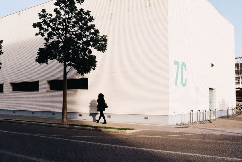 Streetphotography Street Corner Tree Girl Woman Walking Shadow Light And Shadow Figure Lonely Scene Contrast Every Picture Tells A Story Everyday Lives Outdoors Numbers Sign Wall Architecture Building Perspectives Urban Lifestyle Minimalism Solitary Visual Trends SS16 - Urbanity