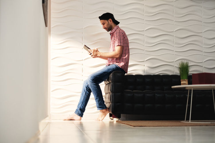 Full length of man using mobile phone at home
