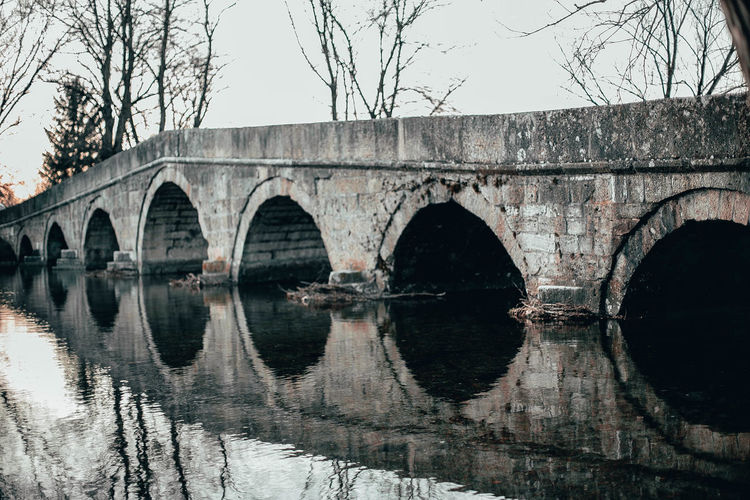 Arch bridge over lake against sky