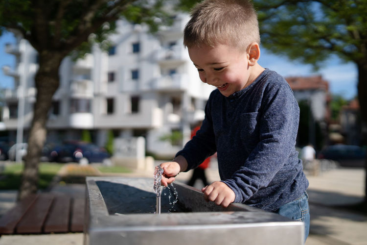 Cute boy drinking water at fountain