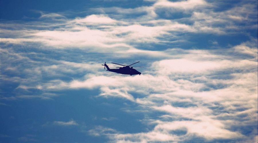 Side view of silhouette helicopter against clouds