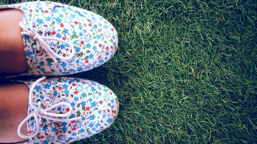Close-up of kid wearing shoes on grass