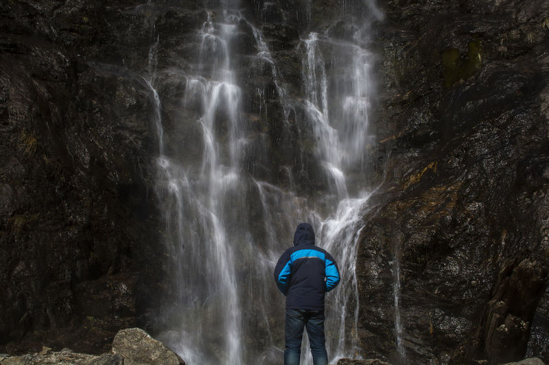 Waterfall Scenics - Nature Rear View Rock One Person Rock - Object Solid Beauty In Nature Water Motion Rock Formation Real People Long Exposure Standing Leisure Activity Lifestyles Adventure Nature Flowing Water Outdoors Looking At View