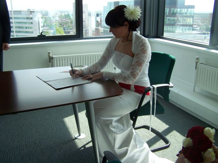 Bride in wedding dress signing document at table