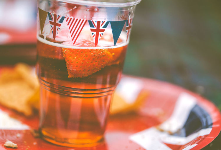 A beer cup decorated with flags on a plate with the British Union jack design on it. Beer Celebration Celebrating Celebration Event Close-up Crockery Cup Drink Drinking Glass Focus On Foreground Food Food And Drink Freshness Glass Glass - Material Household Equipment Mug No People Pint Of Beer Plate Refreshment Still Life Table Tea Cup Union Jack