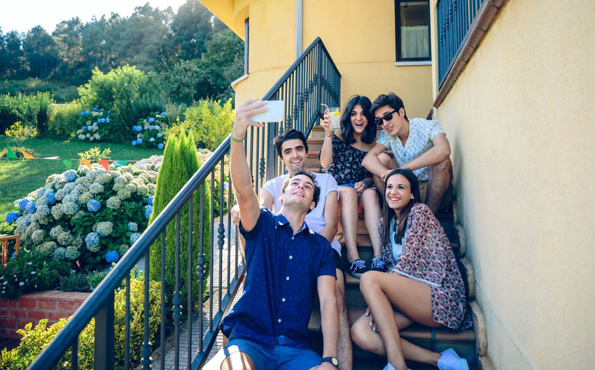 Group of young happy people taking a selfie with a smartphone outdoors sitting on the home stairs steps. Young people lifestyle concept. Fun Happy Home Horizontal Juice Sitting Stairs Taking Photos Young Caucasian Cheerful Five Garden Group Healthy Leisure Mobile Outdoors People Phone Selfie Smartphone Step Summer Sunglasses