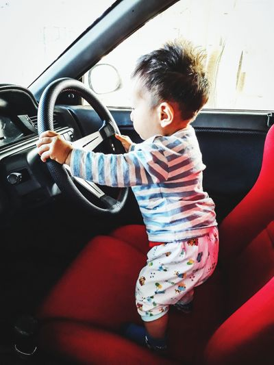 Side view of baby boy playing in car