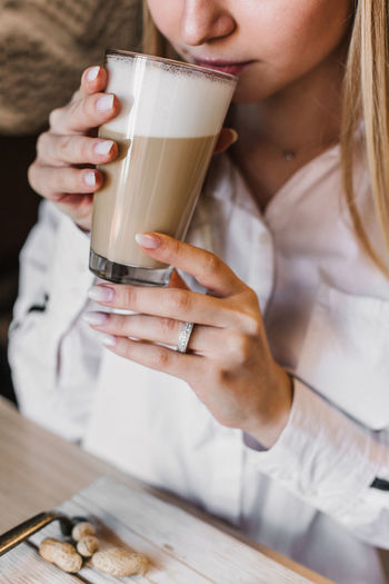Midsection of woman drinking coffee