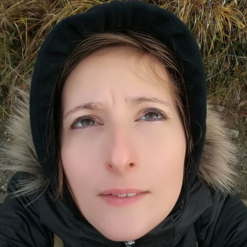 Selfie in the nature and in cold temperature. Young woman in furry hood lying in grass and looking up to sky. Woman Lying On Grass Woman Portrait Nature