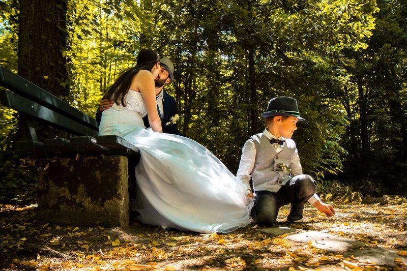 Full Length Of Boy Holding Dress Of Bride Kissing Groom While Sitting On Park Bench
