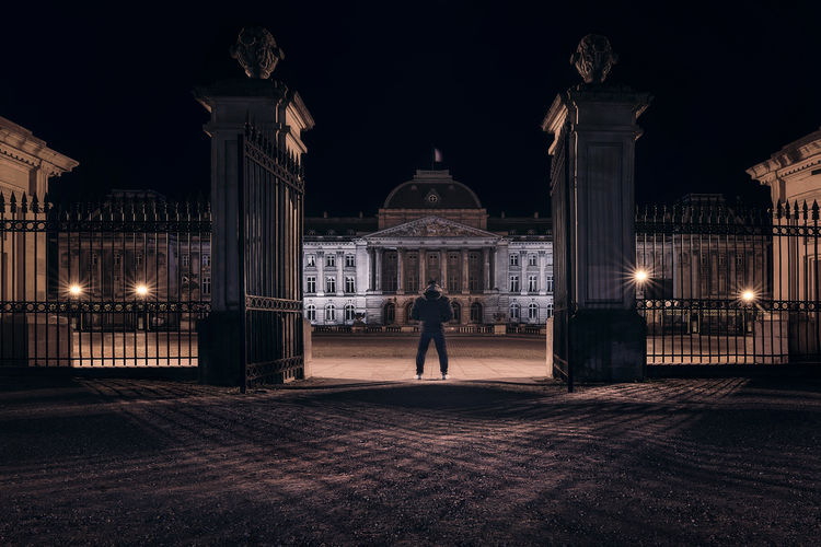 Man standing against building at night