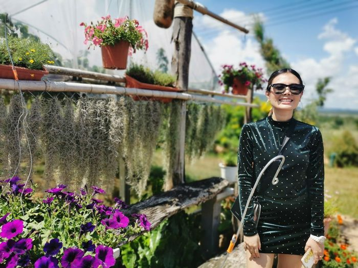 Young woman wearing sunglasses standing by flower plants