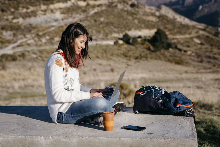 Young woman using mobile phone while sitting on land