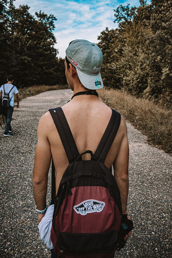 Rear view of man and woman walking on road