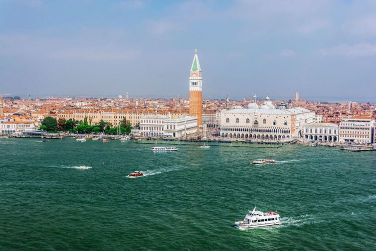 Ferries sailing in grand canal by church of san giorgio maggiore against sky