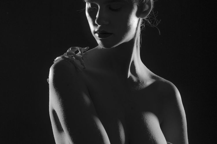 Close-up of shirtless woman with skeleton hand on shoulder against black background