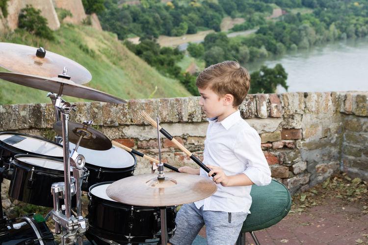 Boy playing drum kit outdoors