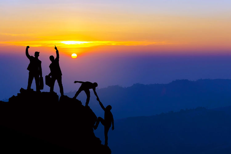 Silhouette Sky Sunset Group Of People Scenics - Nature Mountain Orange Color Beauty In Nature Activity Nature Leisure Activity Rock Rock - Object Standing Real People Tranquil Scene Togetherness Men People Solid Outdoors Mountain Range Sun