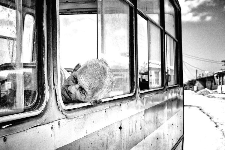 Senior man sleeping at window in bus