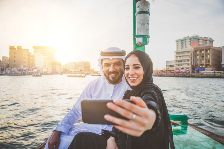 Couple talking selfie while sitting in boat on river during sunset