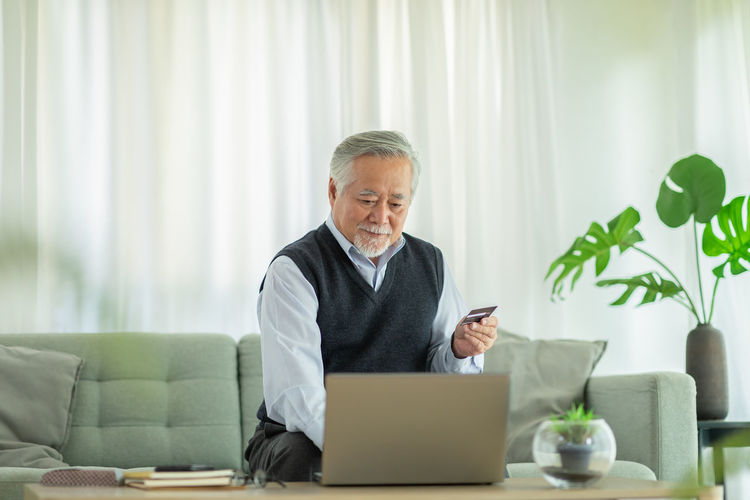 Man using phone while sitting on table