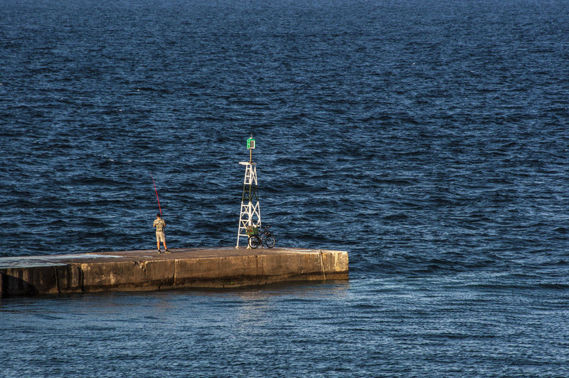 Man Fishing While Standing By Lighthouse