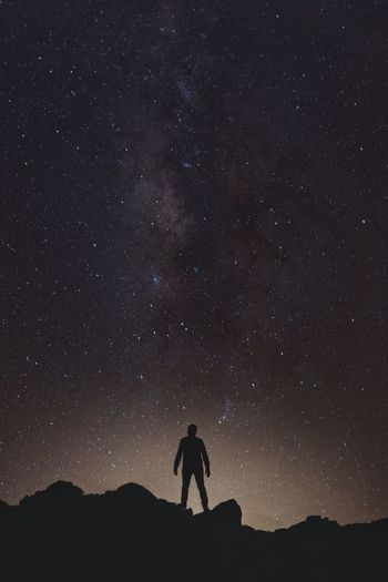 Silhouette man standing on rock formation against milky way