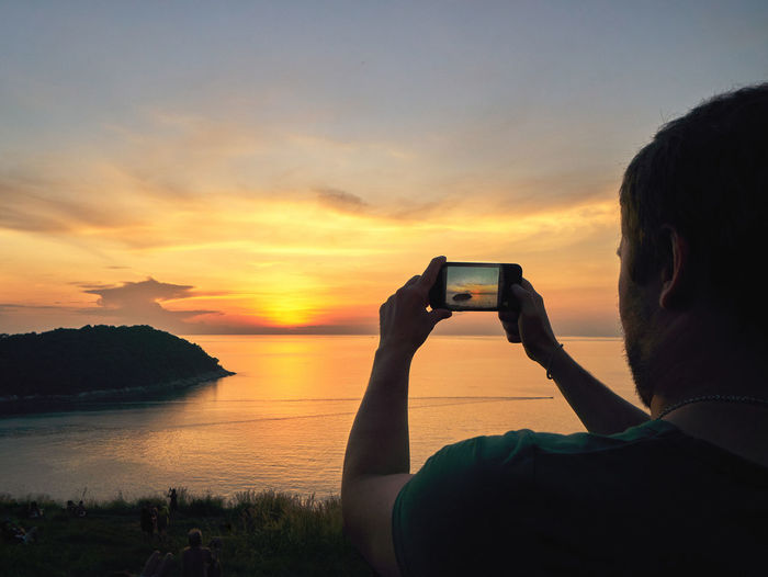 Man photographing at sunset
