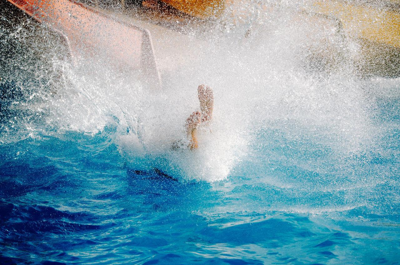 High angle view of man splashing water in pool at aqua paradise ltd water park