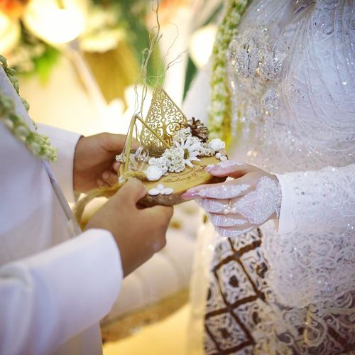 Midsection of couple holding wedding rings