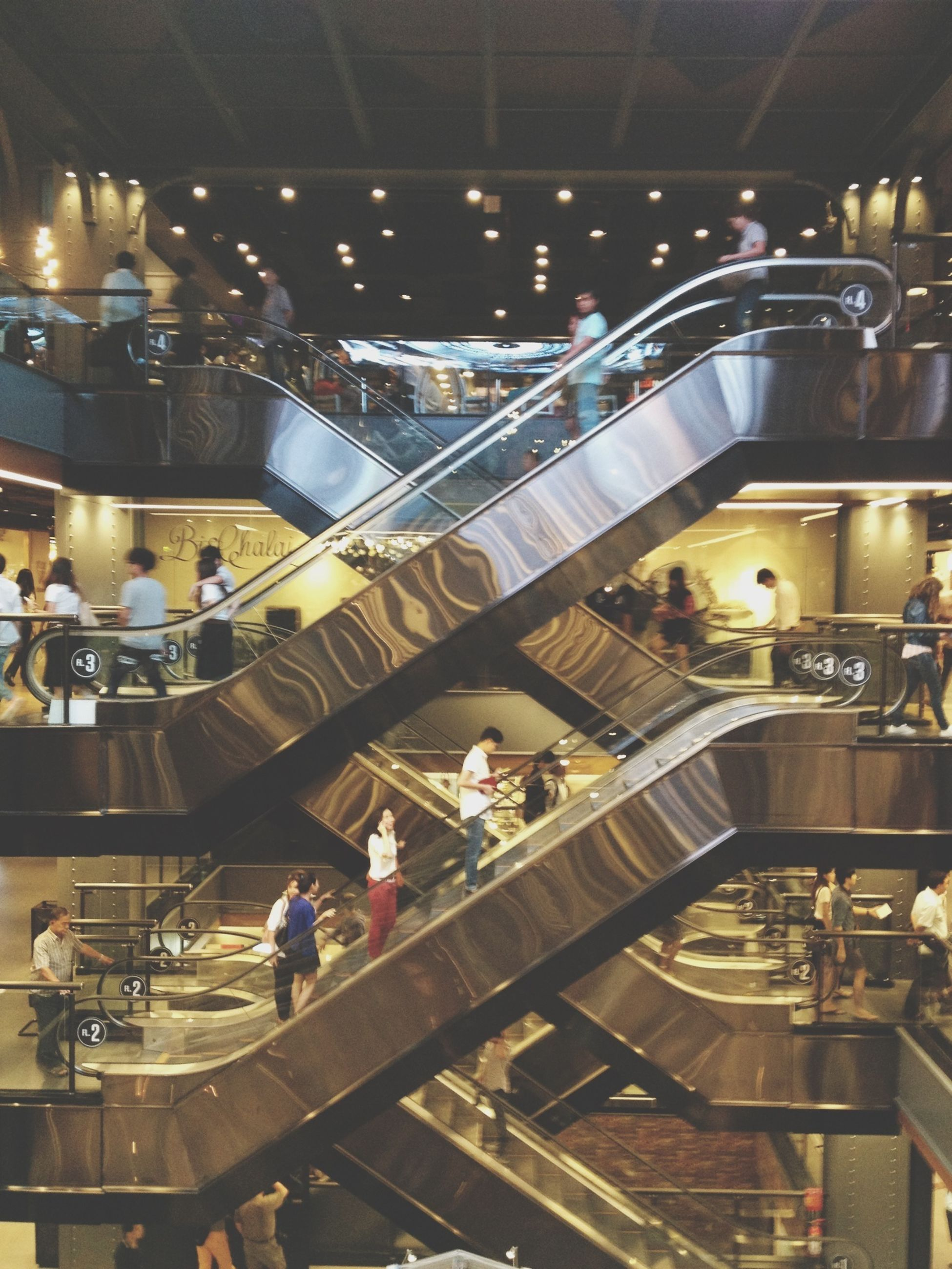 indoors, ceiling, illuminated, men, architecture, built structure, person, large group of people, escalator, steps and staircases, railroad station, incidental people, steps, lifestyles, staircase, high angle view, subway station, leisure activity, travel