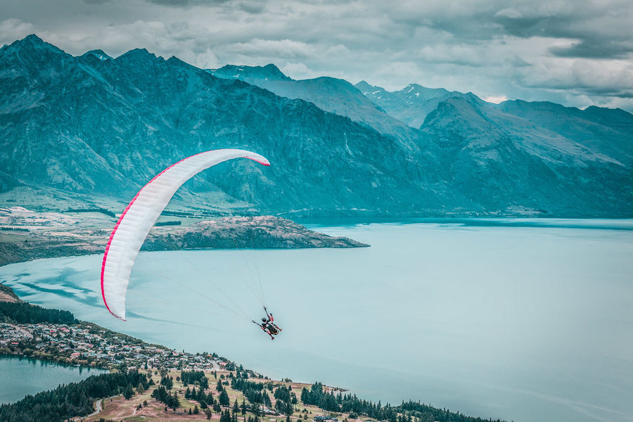 Paragliding with instructor above lake Wakatipu, Queensland, Otago, New Zealand Adventure Day Extreme Sports Flying Landscape Leisure Activity Lifestyles Men Mid-air Mountain Mountain Range Nature New Zealand New Zealand Scenery One Person Outdoors Parachute Paragliding Real People Scenics Sea Sky Sport Vacations Water