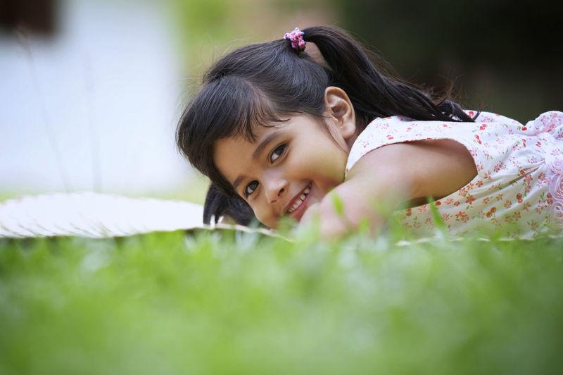 Portrait of smiling girl lying on field
