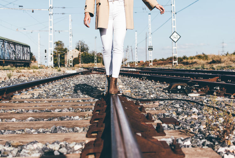 Woman dressed with a beige hat and jacket walking along railroad tracks
