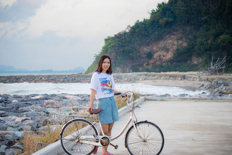 Portrait of young woman riding bicycle on water