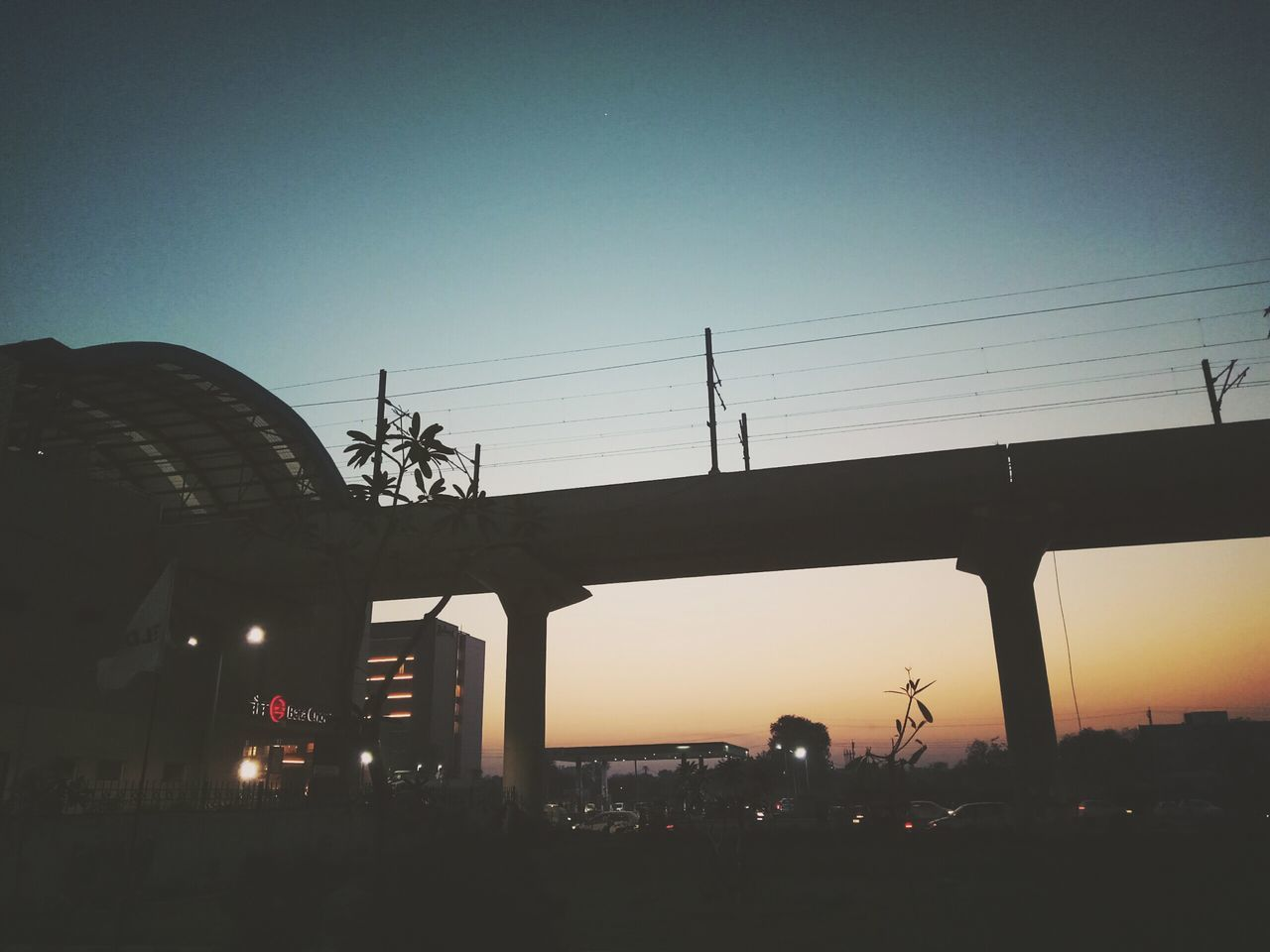sunset, silhouette, built structure, clear sky, architecture, outdoors, sky, city, electricity pylon, nature, day, no people
