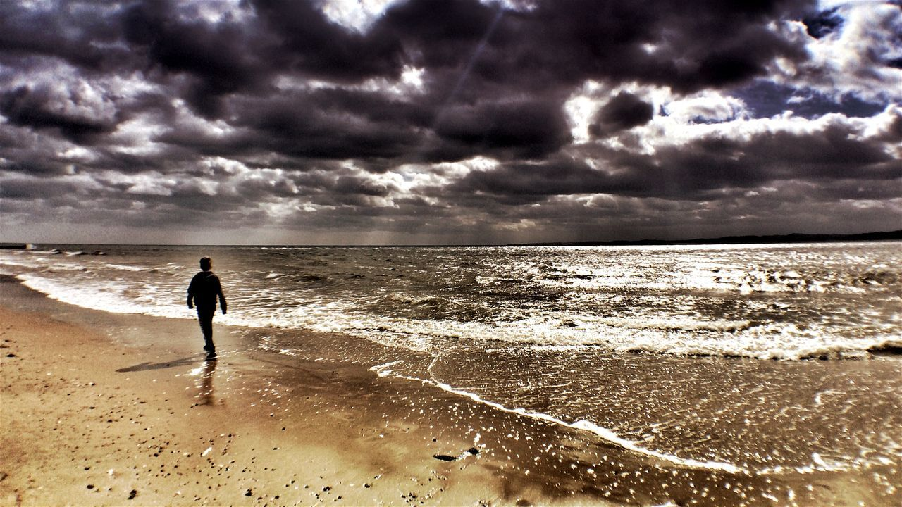Rear View Of Person Walking On Beach Against Cloudy Sky