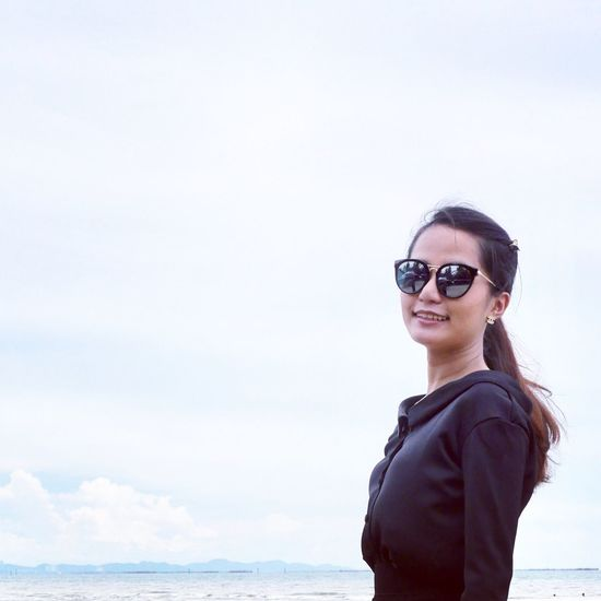 Smiling woman in sunglasses standing at beach against sky