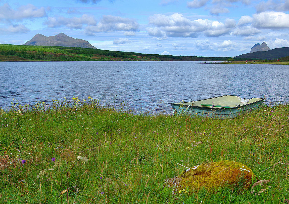 View of Cul Mor and Suilven Assynt Mountains Beauty In Nature Boat Climbing Cloud - Sky Cul Mor Day Fishing Grass Lake Landscape Loch  Loch Borollan Lochinver Marsh Nature No People Outdoors Scenics Scotland Wild Landscape Sky Social Issues Suilven Sutherland Water
